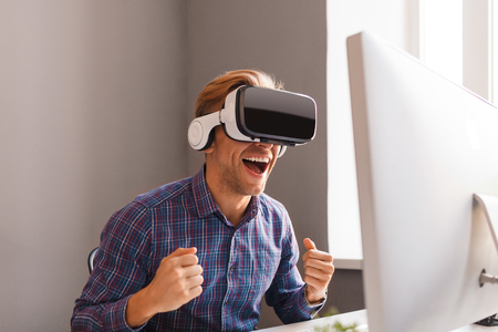 Excited man in VR headset celebrating victory in office