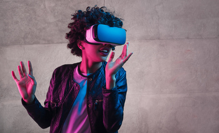 Teenager in VR glasses gesturing and looking away