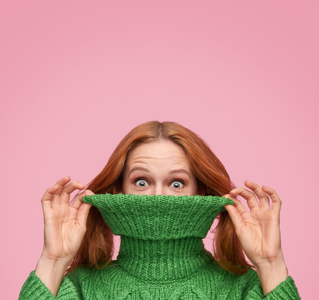 Funny woman pulling sweater neck Imagens