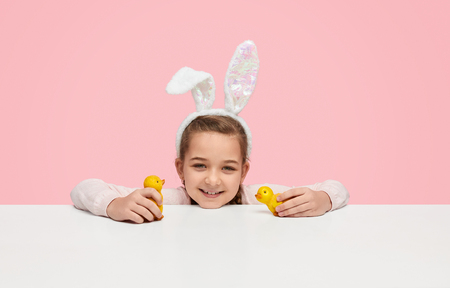 Smiling girl with bunny ears playing with toy chicks