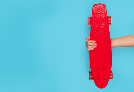 Stylish red longboard on blue background