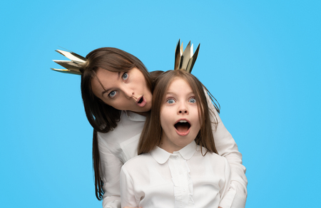 Playful woman and girl in paper crowns Imagens