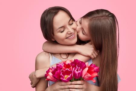 Ragazza che bacia la madre con un bouquet primaverile Archivio Fotografico