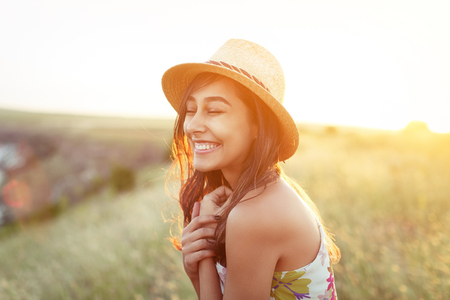 Charming happy girl in hat and dress outdoors Stockfoto