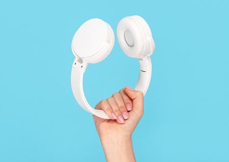 Female hand with stylish white headphones Stock Photo