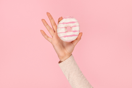 Crop hand holding striped donut