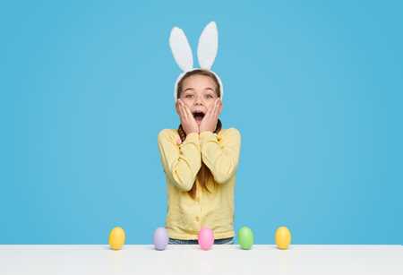 Excited girl with colored eggs on table Stock Photo