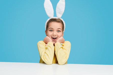 Excited girl in bunny ears looking at camera