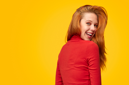 Smiling redhead woman on orange backdrop Stock Photo