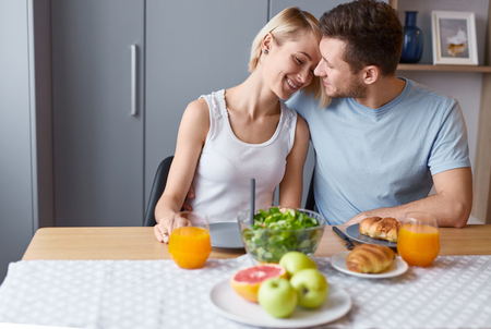 Happy couple embracing at table during breakfast