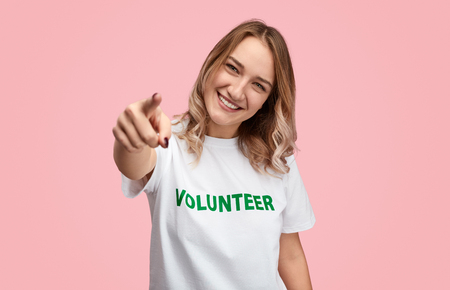 Smiling volunteer pointing at camera Stockfoto