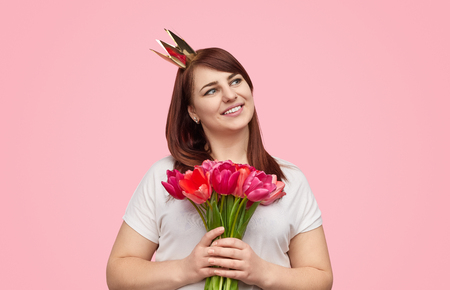 Content plump girl in crown with spring bouquet Stockfoto