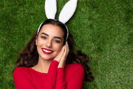 Pretty girl in bunny ears lying on meadow