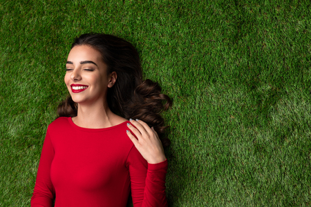Dreamy girl in red dress lying on green grass 版權商用圖片
