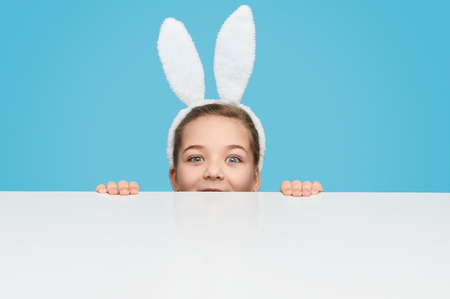 Charming girl in bunny ears hiding behind table
