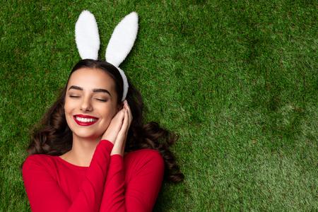 Beautiful dreamy girl in white ears lying on lawn