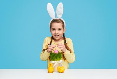 Cute girl finding egg in grass