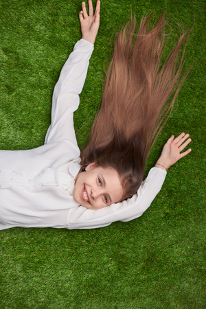 Cheerful girl lying on grass Stock Photo