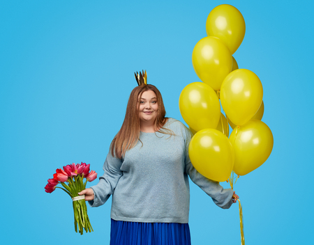 Cute plump woman with balloons and bouquet