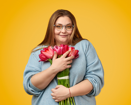 Plus size woman embracing bunch of flowers