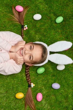 Excited girl lying on grass near Easter eggs Stock Photo