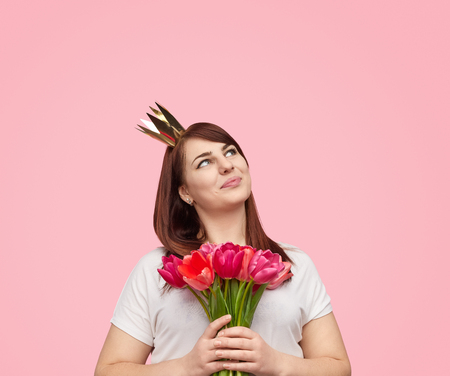 Dreaming plumpy girl in crown holding bouquet