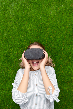Young woman having VR experience on grass