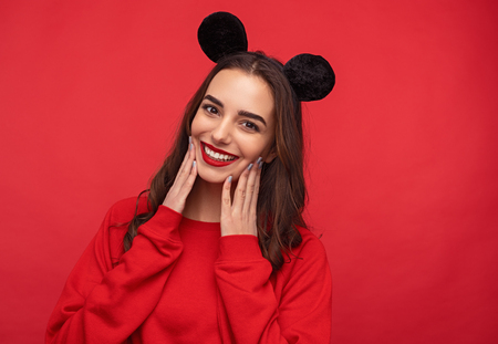 Adorable girl in red sweatshirt and mouse ears