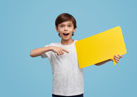 Surprised kid pointing at yellow speech bubble