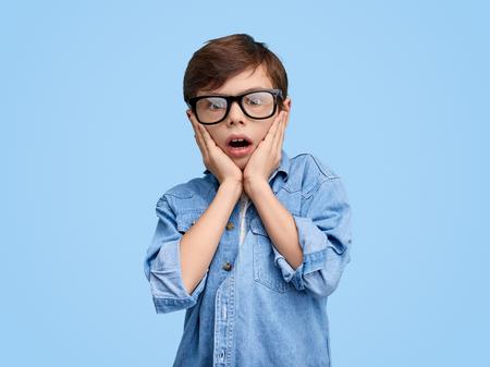 Shocked kid in glasses holding hands on cheeks Stockfoto