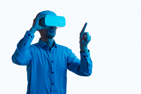 Serious male touching invisible screen in VR Stock Photo