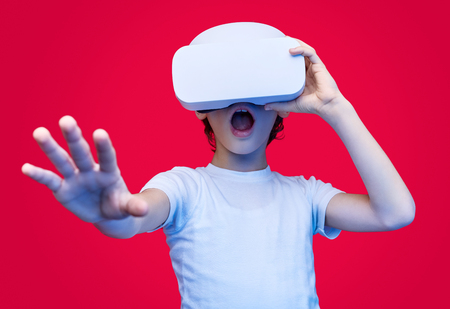 Amazed kid experiencing virtual reality in glasses Stock Photo