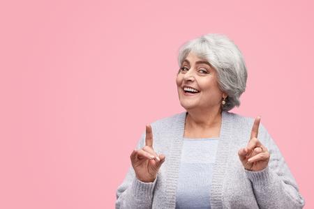 Cheerful senior female pointing up