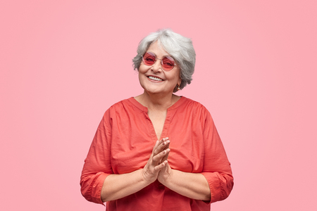 Friendly senior lady with clasped hands Stock Photo