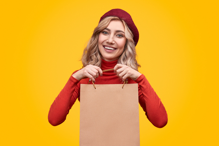 Cheerful lady demonstrating blank paper bag