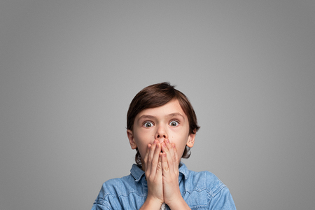 Shocked boy covering mouth