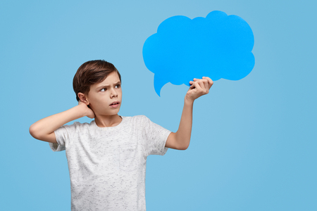 Puzzled kid looking at clear speech bubble Imagens
