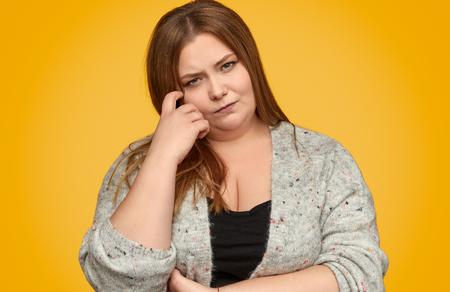 Nachdenkliche dicke Frau, die sich das Gesicht kratzt