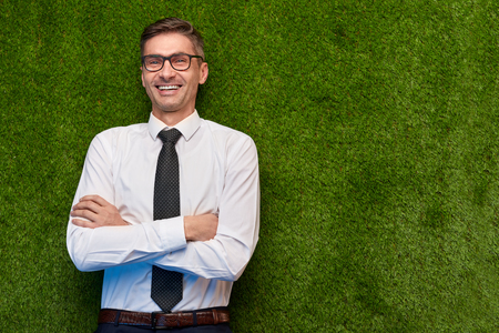 Laughing businessman lying on lawn