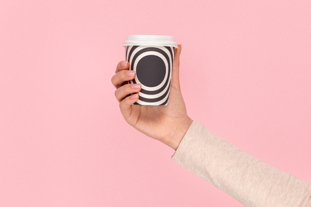 Crop hand holding cup of hot beverage