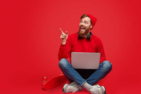 Excited hipster with laptop pointing aside Фото со стока