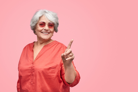Cheerful elderly lady interacting with invisible screen