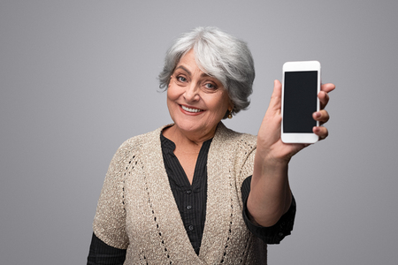 Smiling elderly woman showing smartphone