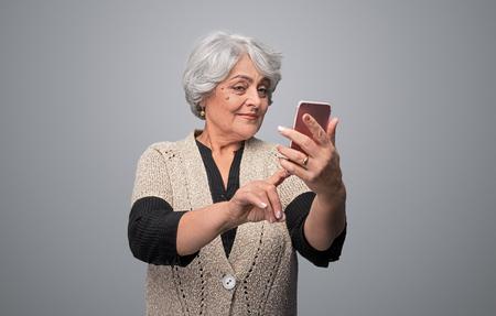 Gorgeous senior woman taking selfie