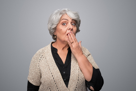 Shocked elderly lady covering mouth