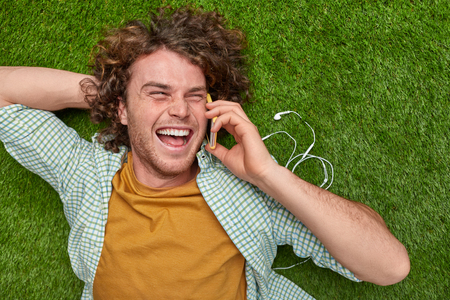 Laughing guy speaking on smartphone on lawn