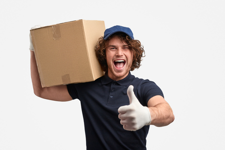 Excited courier with box gesturing thumb up