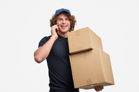 Cheerful courier speaking on phone