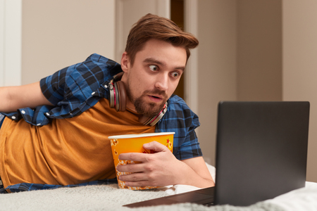 Shocked man with popcorn watching movie Stock fotó