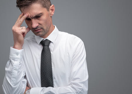 Tired businessman rubbing forehead Imagens